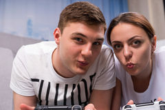 Happy couple lying on a rug and playing video games. Happy couple lying on a rug in their living room playing video games looking towards the camera and pointing Stock Images