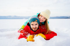 Happy couple lying in snow Stock Images