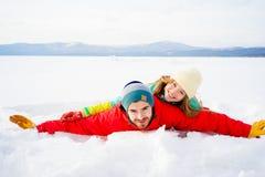 Happy couple lying in snow Royalty Free Stock Photos