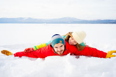 Happy couple lying in snow Royalty Free Stock Images