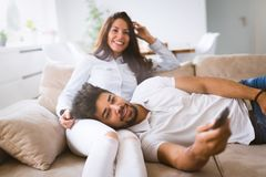 Happy couple lying on sofa together and relaxing at home Stock Photography