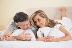 Happy couple lying on their bed and looking at each other Royalty Free Stock Photos