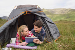 Happy couple lying in their tent and using digital tablet Royalty Free Stock Image