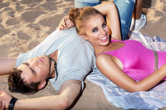 Happy couple lying together on sand - romance Royalty Free Stock Images