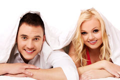 Happy couple lying under blanket looking at camera Stock Photo