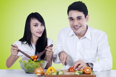 Happy couple make salad together Royalty Free Stock Photo