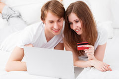 Happy couple makes online shopping with laptop and credit card a Royalty Free Stock Photos