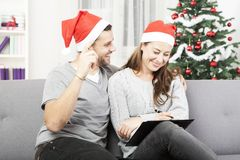 Happy couple makes a wish list for christmas Royalty Free Stock Photos