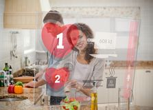 Happy couple making dinner using interface instructions. In the kitchen Stock Photos