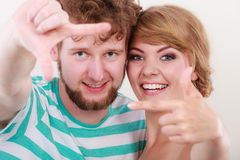 Happy couple making frame with hands Stock Photography