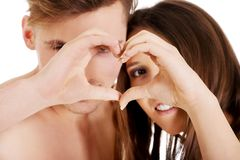 Happy couple making heart with fingers. Royalty Free Stock Photo