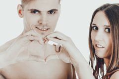 Happy couple making heart with fingers. Royalty Free Stock Photography