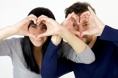 Happy couple making hearts with hands in frond or face showing love Stock Photo