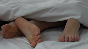 Happy couple making love in bed, legs of husband and wife, intimate relations