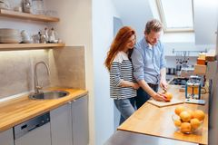 Happy couple making organic juice in kitchen royalty free stock photography