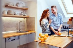 Happy couple making organic juice in kitchen royalty free stock images
