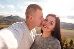 Happy couple making selfie against the mountains. stock images