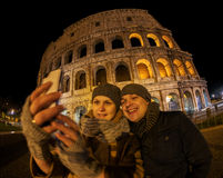 Happy couple making selfie by Coliseum at night. Wide angle shot of happy young couple taking selfie with smart phone near Coliseum at night. Sightseeing in Rome Royalty Free Stock Photography