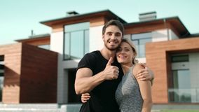 Happy couple making thumbs up near luxury house. Excited family smiling outside