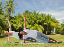 Happy couple making yoga exercises on beach Stock Photos