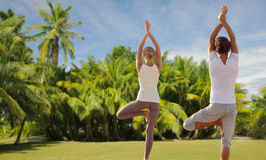 Happy couple making yoga exercises on beach Stock Photo