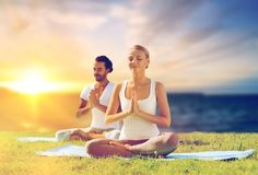 Happy couple making yoga and meditating outdoors. Yoga , mindfulness, harmony and people concept - happy couple meditating in lotus pose outdoors over sea Stock Images
