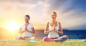 Happy couple making yoga and meditating outdoors. Yoga , mindfulness, harmony and people concept - happy couple meditating in lotus pose outdoors over sea Stock Photo