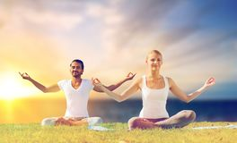 Happy couple making yoga and meditating outdoors. Yoga , mindfulness, harmony and people concept - happy couple meditating in lotus pose outdoors over sea Royalty Free Stock Image