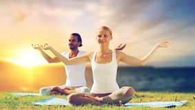 Happy couple making yoga and meditating outdoors. Yoga , mindfulness, harmony and people concept - happy couple meditating in lotus pose outdoors over sea Royalty Free Stock Photo