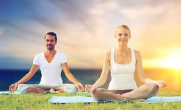 Happy couple making yoga and meditating outdoors. Yoga , mindfulness, harmony and people concept - happy couple meditating in lotus pose outdoors over sea Stock Photos