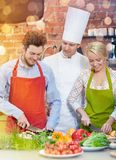 Happy couple and male chef cook cooking in kitchen. Cooking class, culinary, food and people concept - happy couple and male chef cook cooking in kitchen Stock Photography