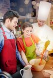 Happy couple and male chef cook cooking in kitchen. Cooking class, bakery, cooking food and people concept - happy couple and male chef cook prepearing cream or Stock Images