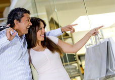 Happy couple pointing inside the store Royalty Free Stock Photo