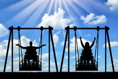 Happy couple, a man, a disabled person and a disabled woman in a wheelchair ride on an adaptive swing. The concept of adaptive equipment for people with stock image