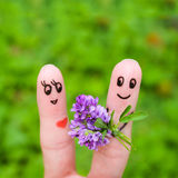 Happy couple. Man is giving flowers to a woman.  Royalty Free Stock Photography