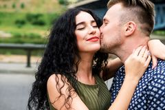 Happy couple, man kissing woman in cheek. Out. Portrait of young happy couple, men kissing women in cheek.  Outdoors Royalty Free Stock Images