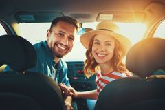 Happy couple man and woman in car traveling in summer stock photography