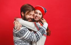 Happy couple man and woman in christmas hats on red backgrou stock photography