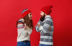 Happy couple man and woman in christmas hats on red backgrou stock images