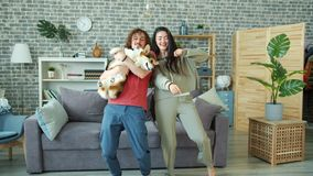 Happy couple dancing at home holding welsh corgi pembroke dog having fun together