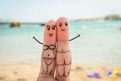 Happy couple. Man and woman have a rest on the beach in bathing suits. Face painted on fingers. Happy couple. Man and woman have a rest on the beach in bathing stock image