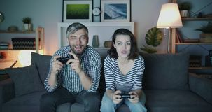 Happy couple man and woman playing video game at home late at night smiling. Sitting on sofa in living room having fun. Modern devices and entertainment concept stock video footage