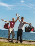 Happy couple man and woman with sport bags. Happy couple men and women with sport gym bags by sea ocean outdoor. Active young girl and guy in training suit Stock Images