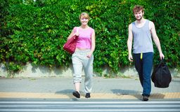 Happy couple man and woman with sport bags. Happy couple men and women with sport gym bags crossing pedestrian crosswalk outdoor. Active young girl and guy in Stock Photos