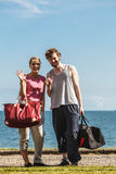 Happy couple man and woman with sport bags. Happy couple men and women with sport gym bags by sea ocean outdoor. Active young girl and guy in training suit Stock Photo