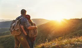 Happy couple man and woman tourist at top of mountain at sunset. Happy couple men and women tourist at top of mountain at sunset outdoors during a hike in summer Royalty Free Stock Image