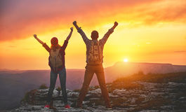 Happy couple man and woman tourist at top of mountain at sunset. Happy couple men and women tourist at top of mountain at sunset outdoors during a hike in summer Stock Photos