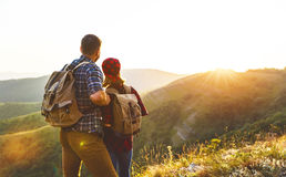 Happy couple man and woman tourist at top of mountain at sunset. Happy couple men and women tourist at top of mountain at sunset outdoors during a hike in summer Royalty Free Stock Photo