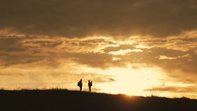 Happy couple man and woman tourist at top of mountain at sunset outdoors during a hike. Silhouettes of two hikers with. Backpacks enjoying sunset. The concept stock video