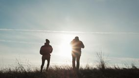 Happy couple man and woman tourist at top of mountain at sunset outdoors during a hike. Silhouettes of two hikers with. Backpacks enjoying sunset. The concept stock footage